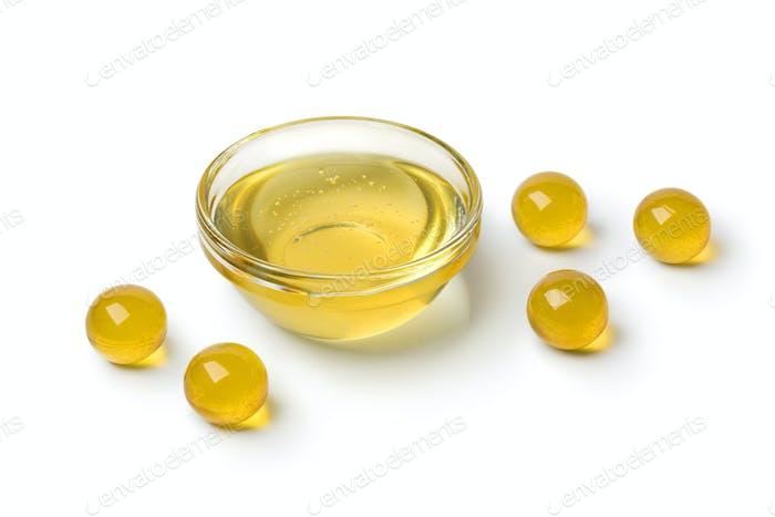 Gelbe Honigperlen und eine Schüssel mit Honig