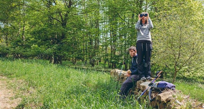 Couple doing trekking looking with binoculars