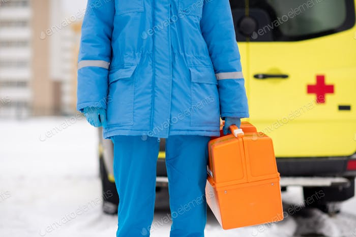 Mid-section of young paramedic in blue workwear and gloves holding first aid kit