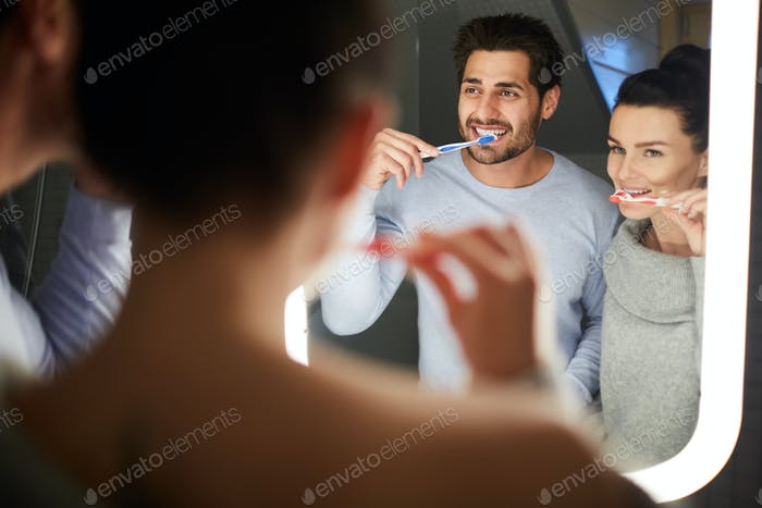Cheerful couple brushing teeth in bathroom