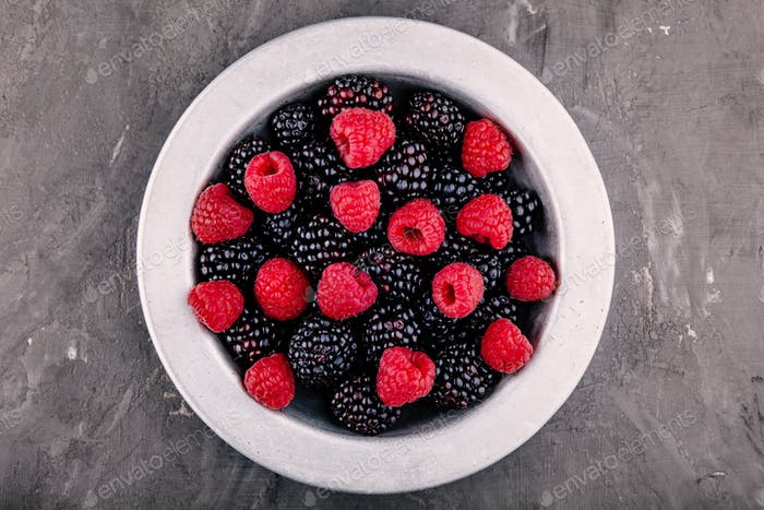 fresh ripe organic raspberries and blackberries in a bowl on a gray background