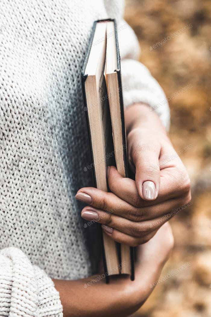 Woman holds a book in her hands, close-up, autumn