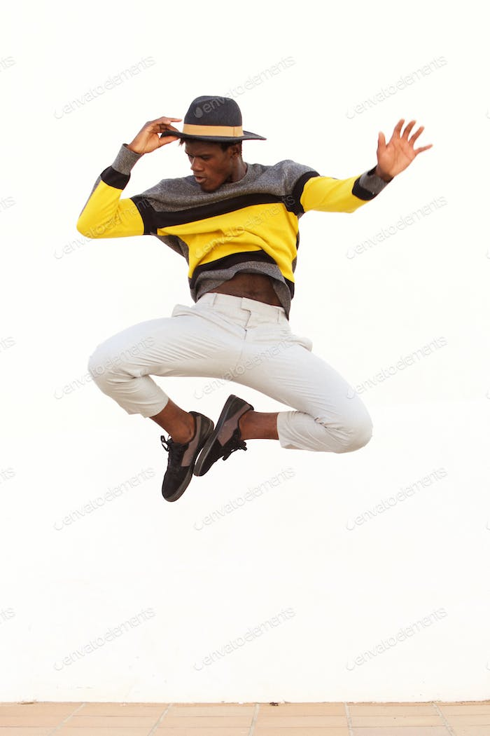 stylish young male dancer jumping and showing his moves on white background