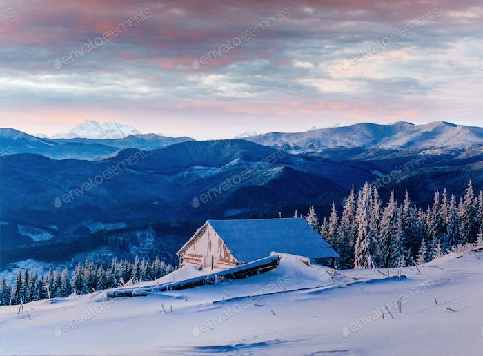 Fantastic sunset over snow-capped mountains and wooden chalets