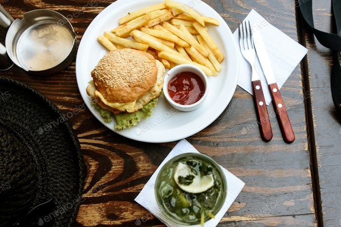 delicious chicken burger with potato fries and ketchup and mojito cocktail