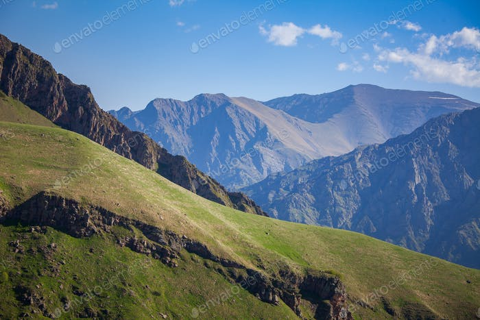 Mountain range and green hill against blue sky