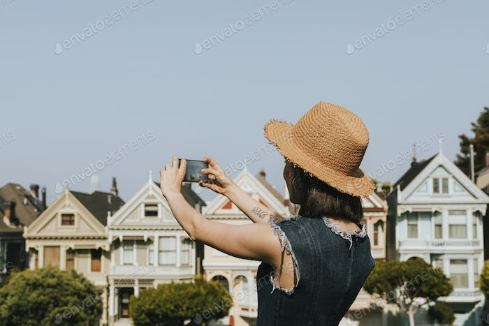 Woman taking a photo of the Painted Ladies of San Francisco, USA