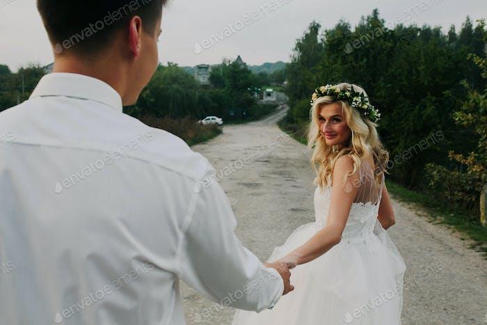 bride leads groom on the road
