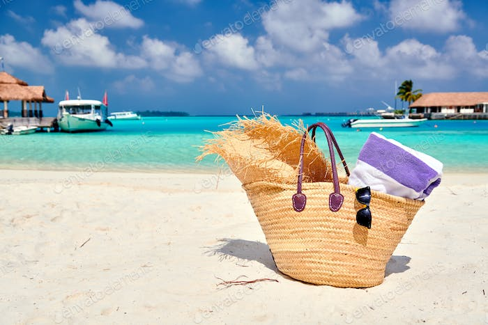 Straw bag with hat and towel on beach