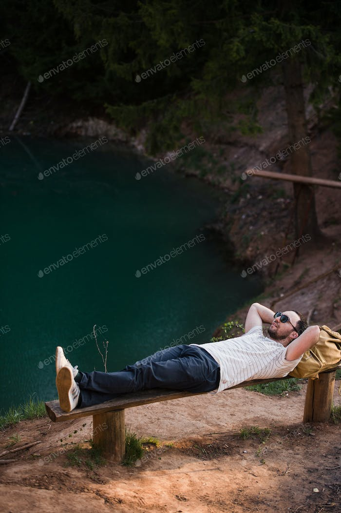 Man Relaxing Outside on a bench near lake