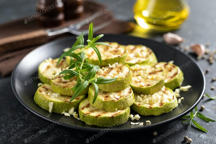 Grilled zucchini, courgette with garlic and rosemary on plate