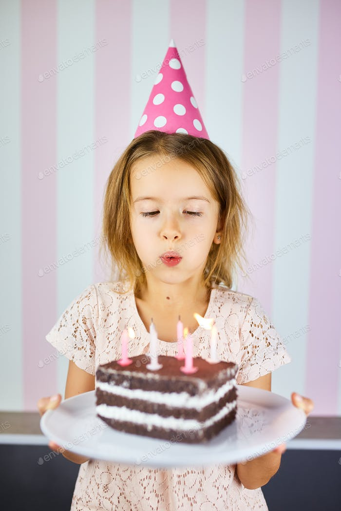 Little girl in pink cap blowing out candles on a birthday chocolate cake