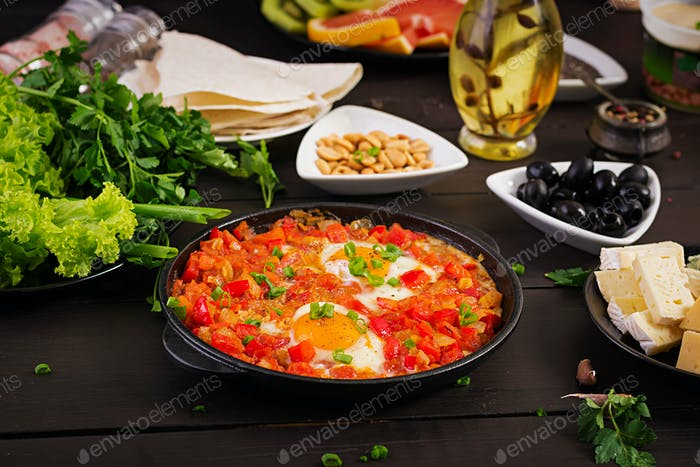 Turkish Breakfast -  shakshuka, olives, cheese and fruit. Rich brunch.