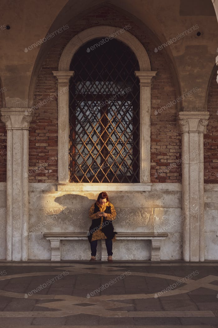 Woman sitting on a bench underneath arched window in Venice, Veneto, Italy.