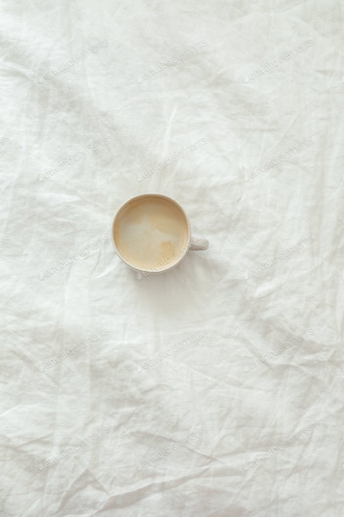 Cup of fresh coffee on texture of linen cotton rough textile bedclothes
