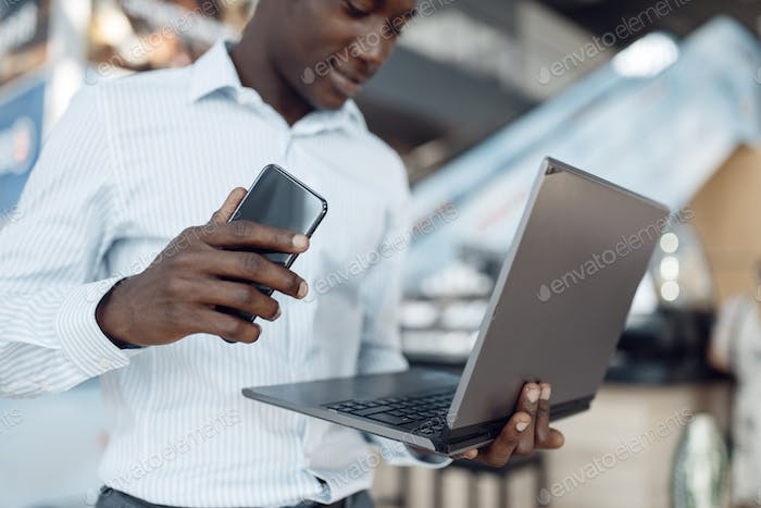 Businessman using laptop and phone in car showroom