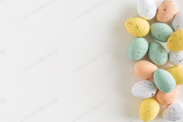 A beautiful spread of chocolate easter egg in pastel colors,white background, copy space