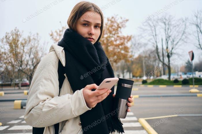 Attraktive lässige Mädchen mit Handy zuversichtlich suchen in der Kamera
