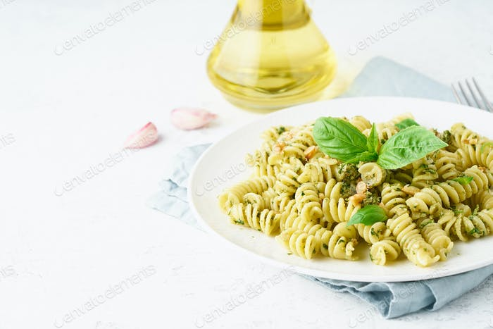 fusili pasta with basil pesto and herbs, italian cuisine, gray stone background, side view
