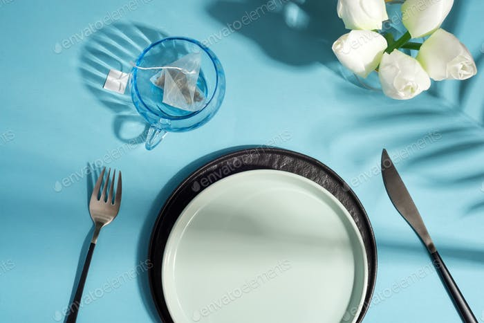 Dinner table with ceramic plate served knife and fork