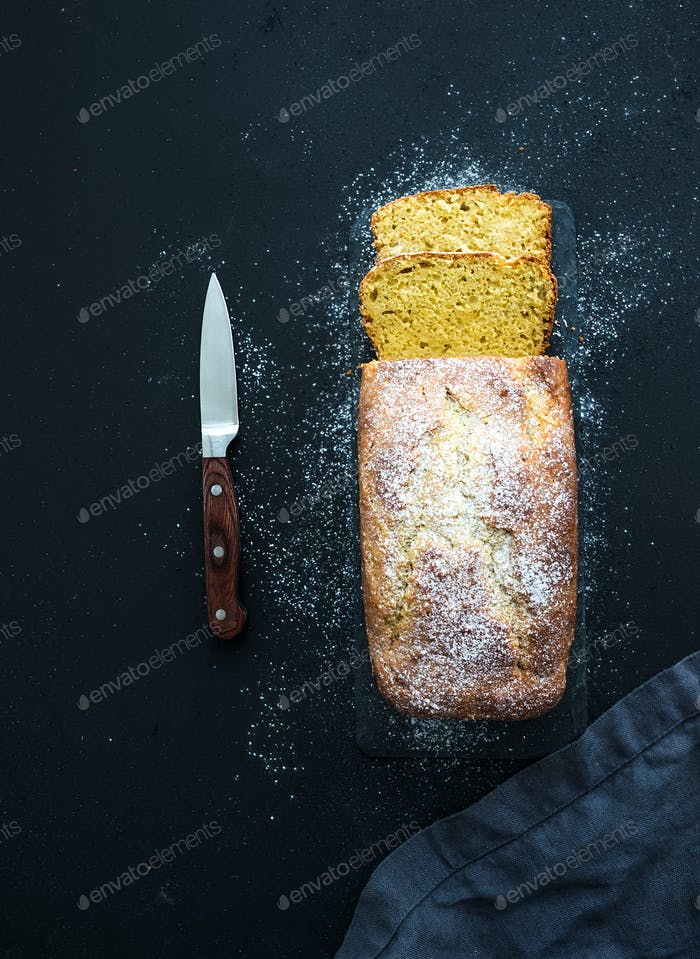Lemon pound cake with sugar powder cut into pieces on dark slate board over black backdrop.