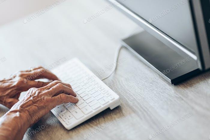 Ältere Frau, die auf einer Tastatur tippt