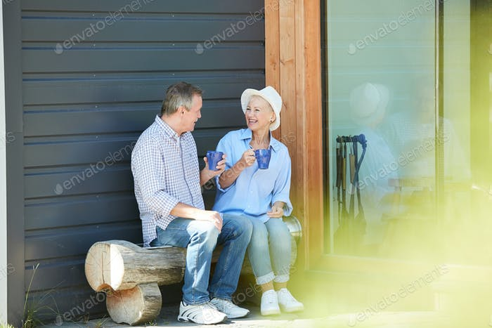 Senior Couple Drinking Tea in Front Yard