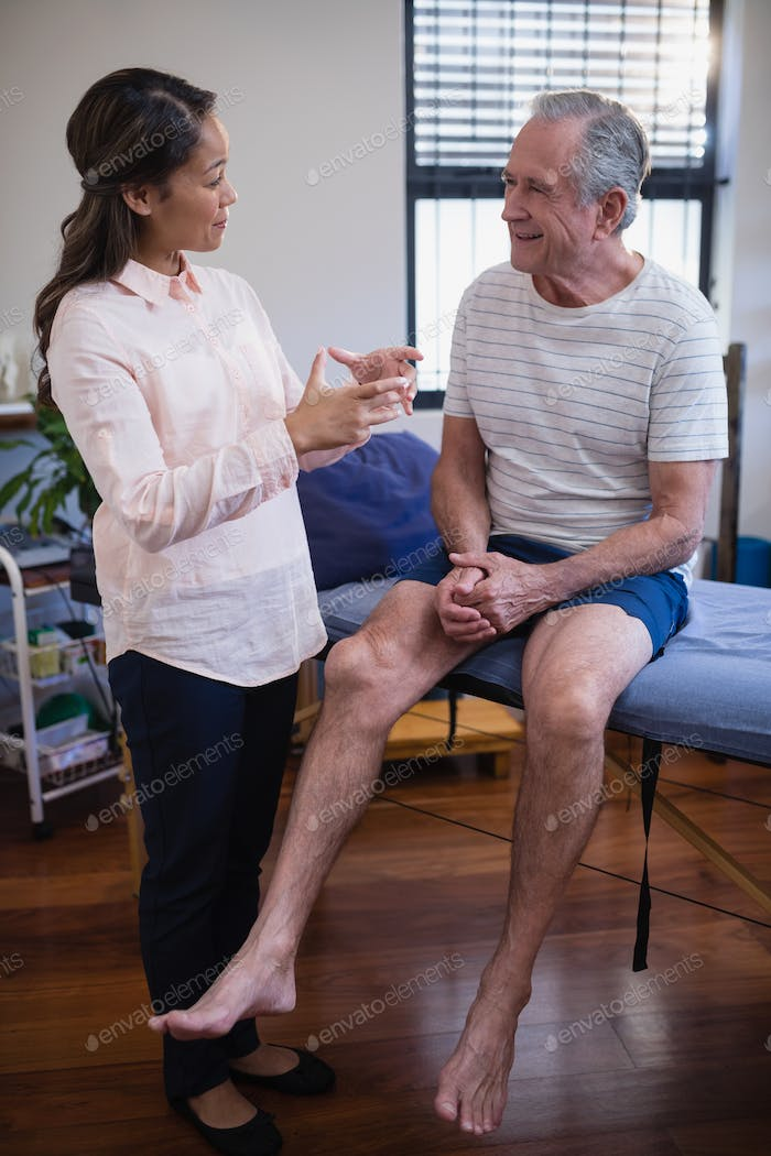 Female therapist gesturing while talking with senior male patient sitting on bed