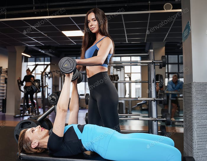 Professional trainer supporting his customer in gym