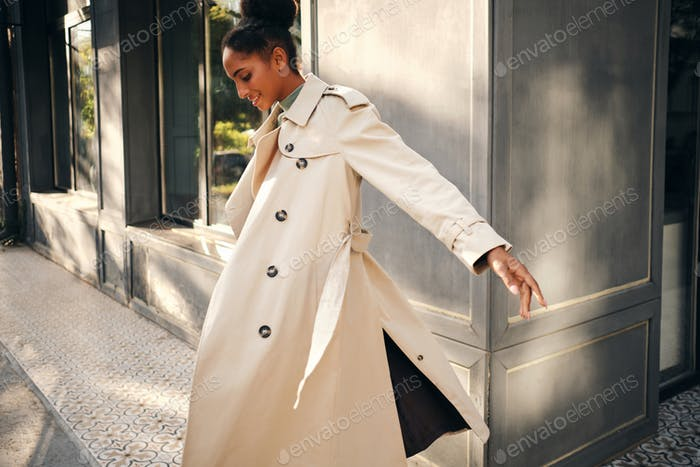 Attractive casual African American girl in stylish trench coat happily whirling on city street