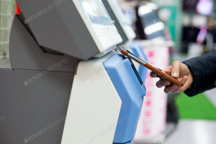 Woman using smart phone for paying on machine by NFC