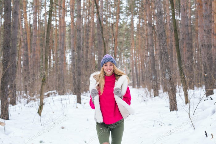 Season, nature, people concept - a beautiful blond woman running in winter wood and smiling