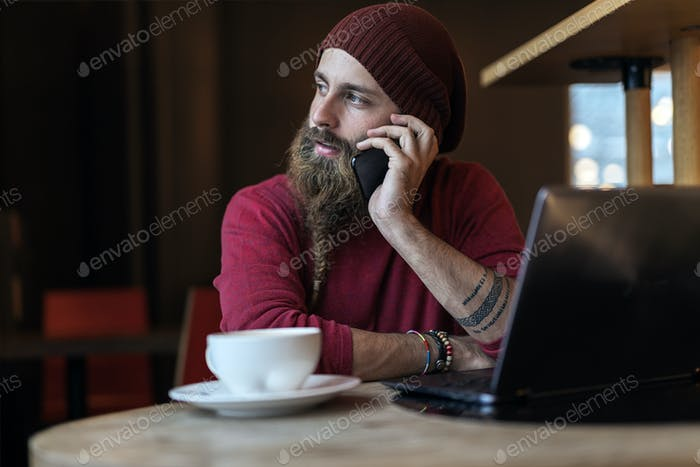 Bearded hipster speaking on phone
