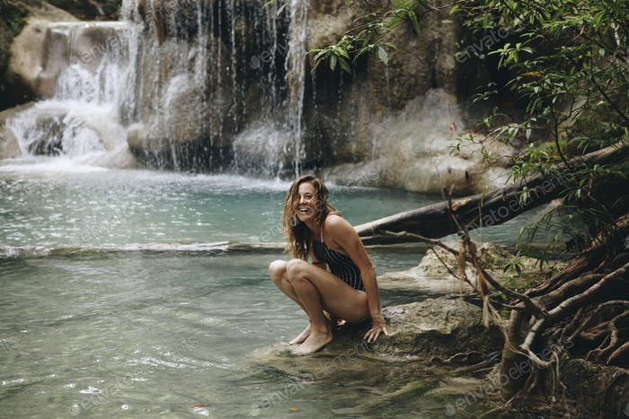 Woman sitting in a natural pond