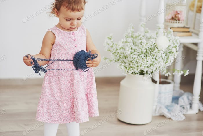Childhood concept. Baby girl in cute dress play with colored thread. White vintage childroom