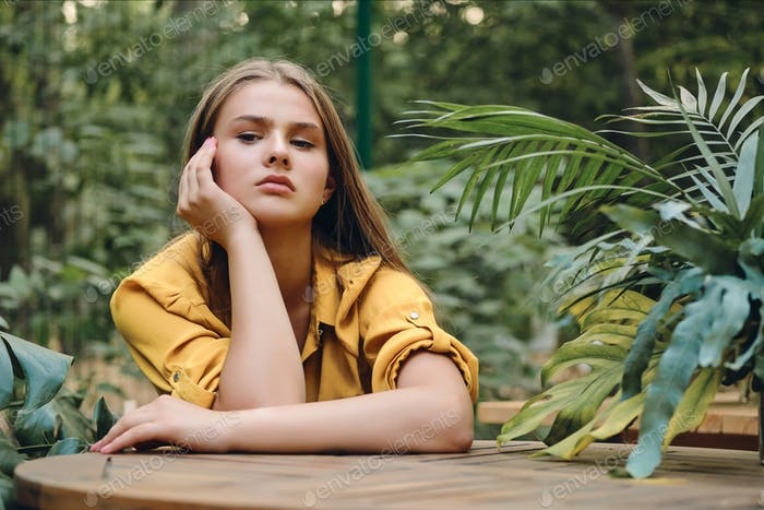 Young upset brown haired woman in yellow shirt thoughtfully sitting among green leaves in park