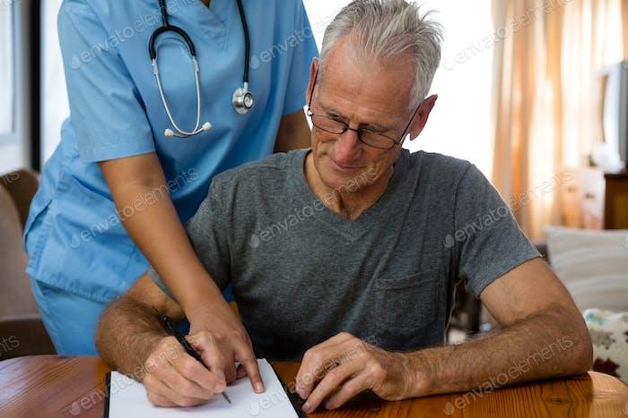 Female doctor assisting senior man in writing at nursing home