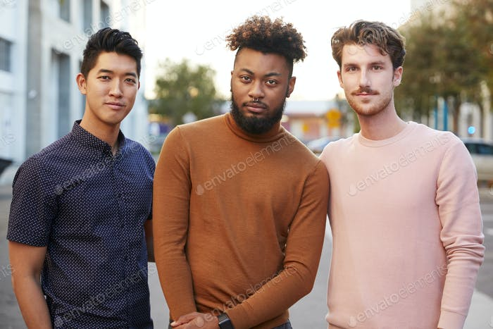 Three hip young adult male friends standing in a city street looking to camera, front view, close up