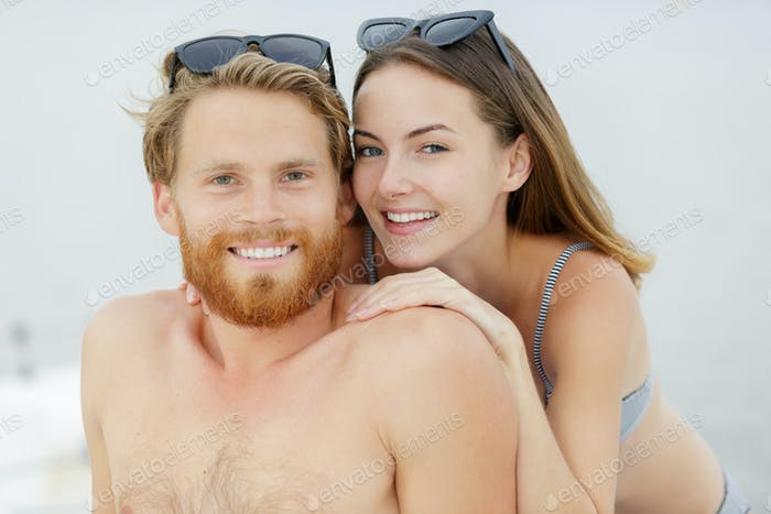 couple smiling on the beach on a sunny day