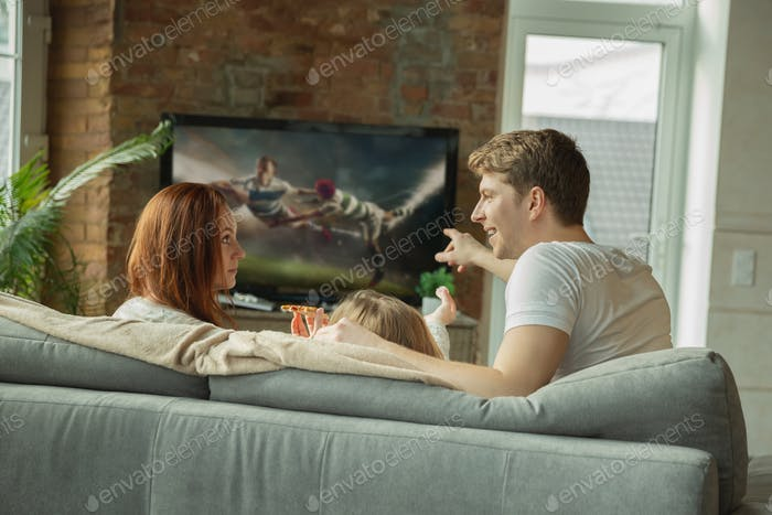 Family spending nice time together at home, looks happy and excited, eating pizza, watching rugby