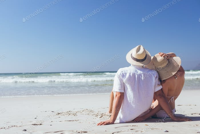 Young Caucasian couple relaxing sitting face to the sea at beach on a sunny day. They wear hats