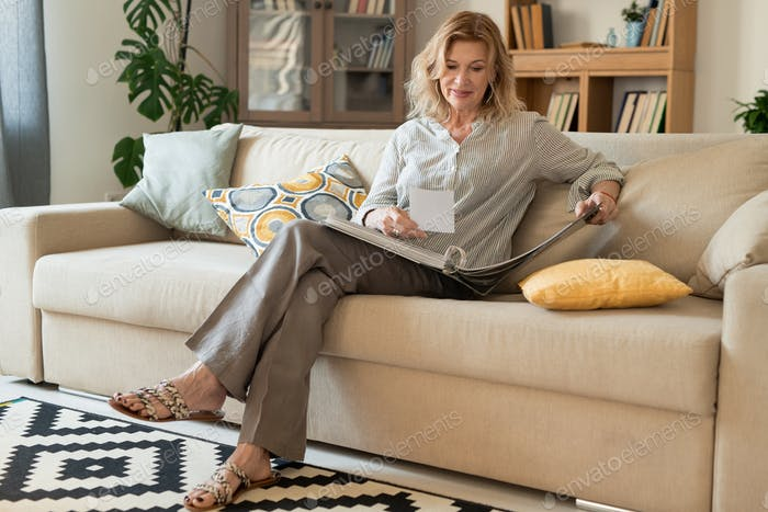 Happy mature woman with blond hair looking through albums with family pictures