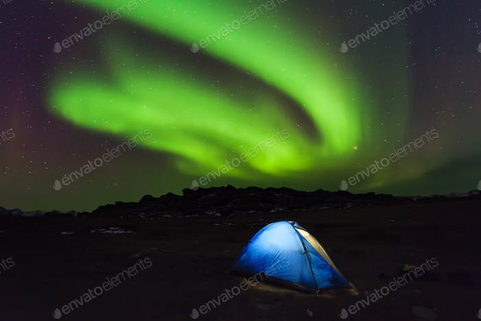 Camping in the north with the northern lights overhead