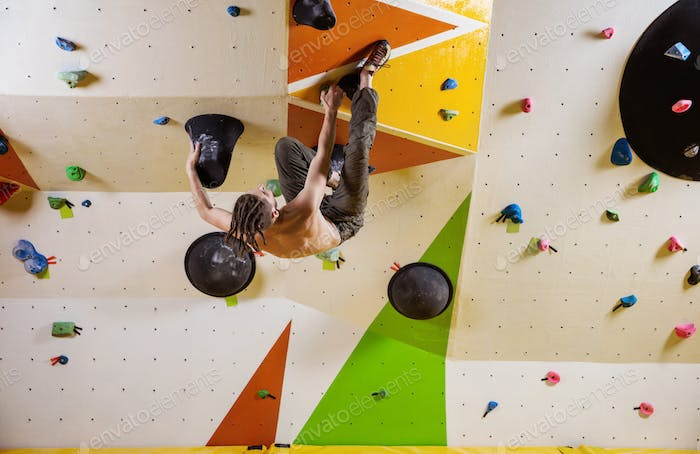 Young man climbing challenging bouldering route