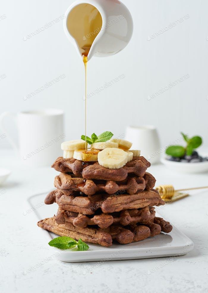 Schokoladen-Bananenwaffeln auf weißem Tisch, vertikal. Süßer Brunch, Ahornsirup Flow