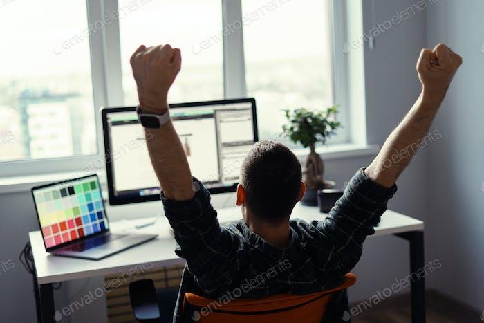 Siegerischer Mann feiert seinen Erfolg an seinem Arbeitsplatz