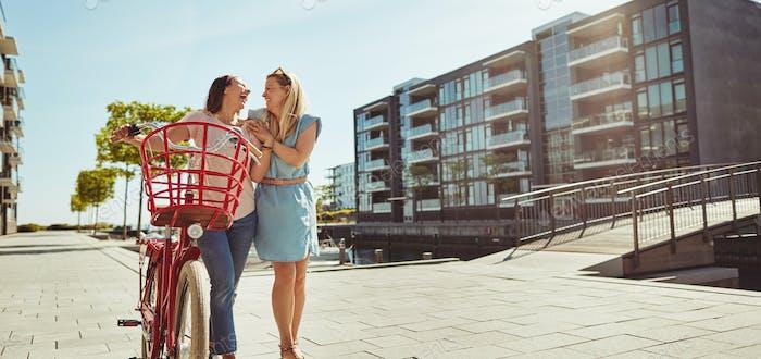 Lachende Freundinnen zu Fuß mit dem Fahrrad im Sommer