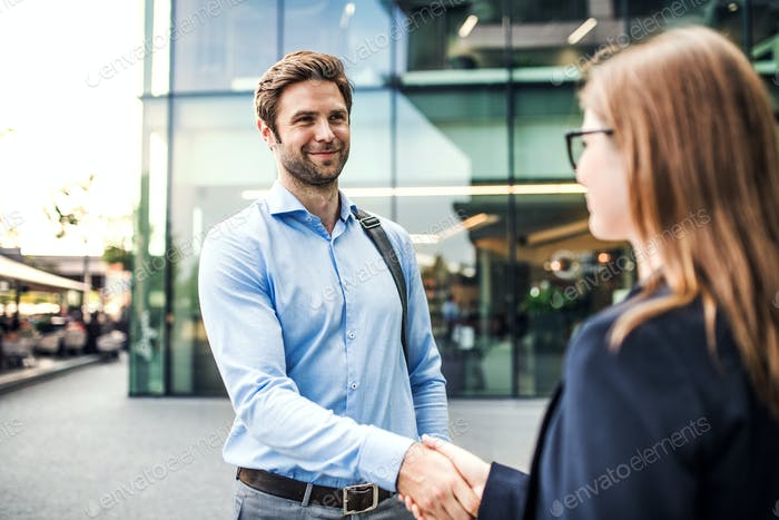 A young businessman and businesswoman shaking hands.