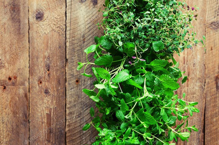 Collection of fresh organic herbs (melissa, mint, thyme, basil, parsley) on wooden background
