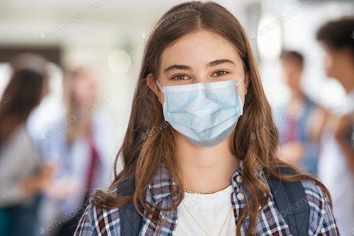 Happy student girl at high school wearing face mask
